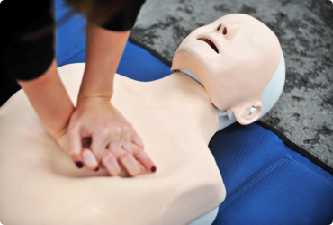 An employee practices CPR on a dummy